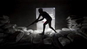 Mumbaj (Indie). Robotnik w trakcie rozładunku wagonów z cementem.