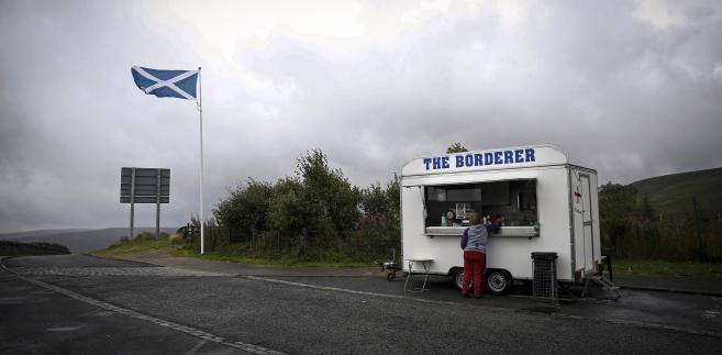 Szkocka flaga narodowa powiewająca w pobliżu granicy Szkocji i Wielkiej Brytanii.
