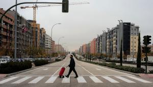 Mieszkaniec Madrytu przechodzi przez ulicę na jednym z osiedli mieszkaniowych