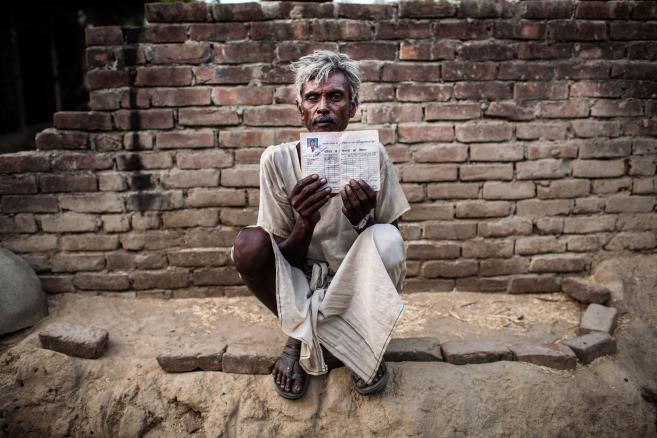 Ram Kishen, mieszkaniec wioski Satnapur w indysjkim stanie Uttar Pradesh pokazuje dokument uprawniający do przydziału żywności