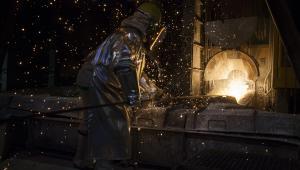 Pracownik huty otwiera piec do wytopu metali