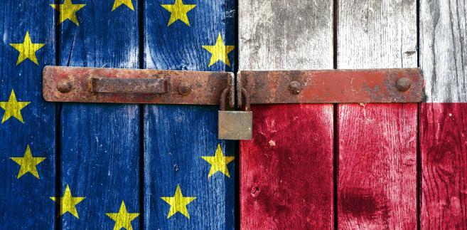 Flagi EU i Polski za zamkniętych na kłódkę drzwiach